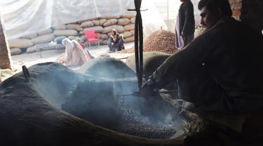 Seorang pedagang Pakistan memanggang kacang pinus di pasar di Lahore (13.12). Pakistan merupakan salah satu penghasil kacang pinus terbaik di dunia. (AFP Photo/Arif Ali)
