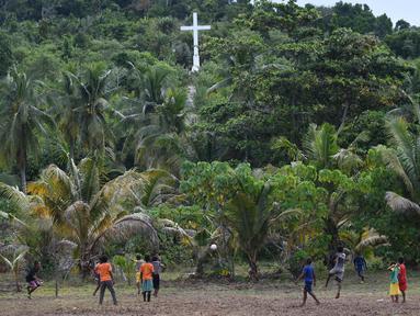 Sejumlah anak dari suku Byak Betew bermain sepak bola setelah misa hari Minggu di pulau Saukabu, satu dari 1.500 pulau di Raja Ampat 20 Agustus 2017. Raja Ampat  yang berarti Empat Raja terdiri dari 1.500 pulau. (AFP Photo/Goh Chai Hin)