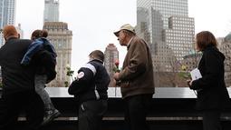 Orang-orang menaruh bunga mawar dalam peringatan 25 tahun serangan bom truk di WTC, New York City, Amerika Serikat, Senin (26/2). Bom yang meledak di garasi parkir bawah tanah tersebut diluncurkan oleh ekstremis. (Spencer Platt/Getty Images/AFP)