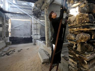 Seniman asal Belanda, Marjan Teeuwen terlihat memanjat tangga saat menciptakan sebuah karya arsitektur dari reruntuhan rumah yang hancur bekas perang pada 2014 di Khan Younis, selatan Jalur Gaza, 12 November 2016. (REUTERS/Ibraheem Abu Mustafa)