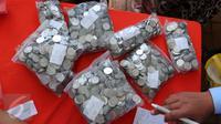 Sejumlah uang logam milik warga yang akan ditukarkan di penukaran uang keliling di Lapangan IRTI Monas, Jakarta, Senin (13/6). BI dan 20 bank umum membuka pelayanan penukaran uang di Monas yang dimulai 10 Juni 2016 kemarin. (Liputan6.com/Angga Yuniar)