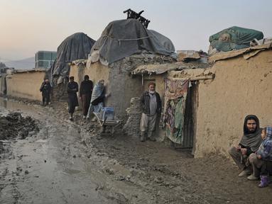 Seorang pria Afghanistan duduk di dinding ketika yang lain berjalan melalui jalan berlumpur di sebuah kamp di Kabul, Afghanistan (27/11/2019). Puluhan ribu warga Afghanistan yang terlantar secara internal tinggal di kamp-kamp, yang kekurangan fasilitas dasar, di Afghanistan. (AP Photo/Altaf Qadri)