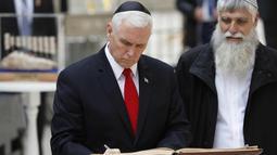Wakil Presiden AS Mike Pence (kiri) menandatangani buku tamu saat berkunjung ke Tembok Barat Yerusalem (23/1). Mike Pence berjanji untuk memindahkan kedutaan ke kota yang disengketakan tersebut pada akhir tahun 2019. (AFP Photo/Thomas Coex)