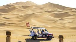 Para wisatawan menjelajahi kawasan wisata Gurun Kum Tag dengan sebuah kendaraan di Wilayah Shanshan, Kota Turpan, Daerah Otonom Uighur Xinjiang, China barat laut (22/9/2020). Gurun tersebut saat ini mencatat peningkatan arus wisatawan. (Xinhua/Wang Fei)