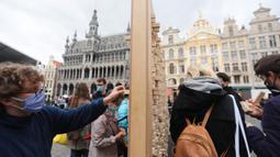 """Orang-orang mengambil sejumlah balok kayu dari """"The Disappearing Wall"""" di Grand Place, Brussel, Belgia, 3 Oktober 2020. Instalasi seni memperingati 30 tahun reunifikasi Jerman itu terdiri dari 6.000 balok kayu dilengkapi kutipan para seniman dan pemikir dari seluruh dunia. (Xinhua/Zheng Huansong)"""