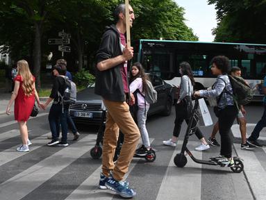 Arshavir Grigoryan yang memiliki tinggi tubuh 2 meter 33 centimeter berjalan saat berkumpul di Champs-Elysees Avenue di Paris, Prancis (14/6/2019). Sambil membawa poster, belasan pria tertinggi dunia berkumpul pada akhir pekan di Champs-Elysees Avenue. (AFP Photo/Dominique Faget)