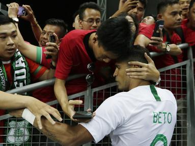 Seorang suporter memeluk striker Timnas Indonesia, Beto Goncalves, usai dikalahkan Singapura pada laga Piala AFF di Stadion Nasional, Singapura, Jumat (9/11). Singapura menang 1-0 atas Indonesia. (Bola.com/M. Iqbal Ichsan)