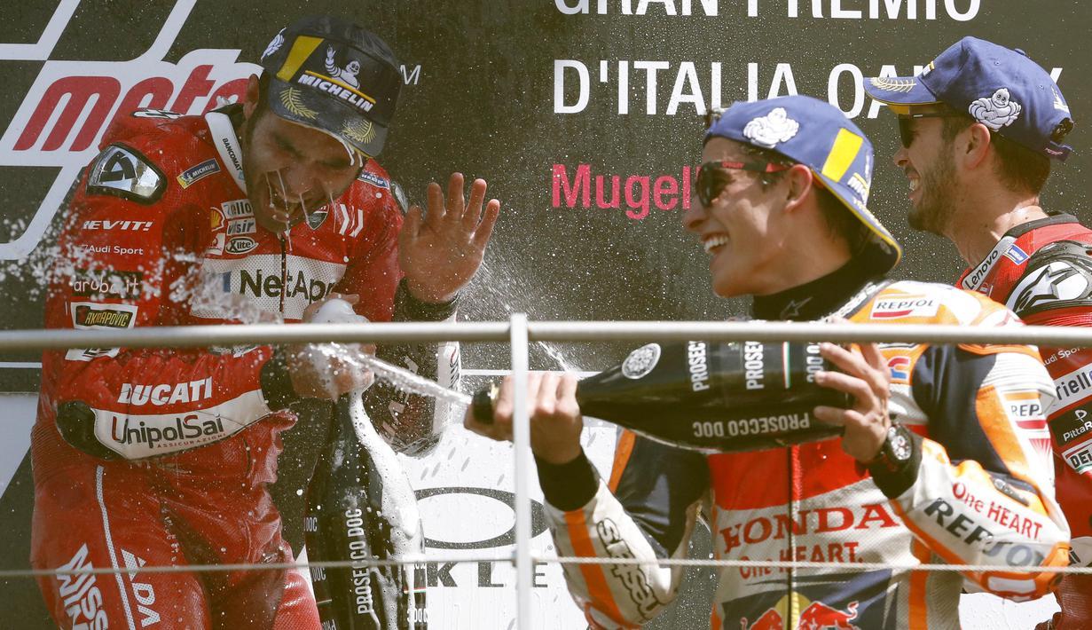 Pebalap Ducati, Danilo Petrucci, bersama Marc Marquez dan Andrea Dovizioso melakukan selebrasi usai menjuarai MotoGP Italia 2019 di Sirkuit Mugello, Minggu (2/6). Petrucci mencatatkan waktu 41 menit 33,794 detik. (AP/Antonio Calanni)
