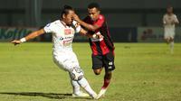 Pemain Persipura Jayapura, Todd Rivaldo Ferre (kanan) berebut bola dengan pemain Persija Jakarta, Tony Sucipto dalam laga pekan ke-3 BRI Liga 1 2021/2022 di Stadion Indomilk Arena, Tangerang, Minggu (19/9/2021). (Bola.com/Ikhwan Yanuar)