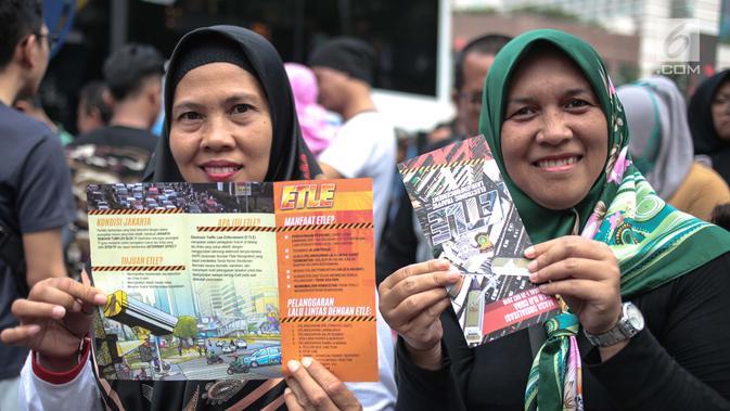 Warga menunjukkan brosur sosialisasi tilang elektronik saat car free day di bunderan HI, Jakarta, Minggu (28/10). Kegiatan sosialisasi E-Tilang tersebut agar masyarakat lebih mengetahui sanksi yang akan diberikan. (Liputan6.com/Faizal Fanani)