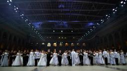 Para siswa sekolah militer bersiap untuk menari saat pesta tahunan Cadet Ball di Moskow, Rusia, Selasa (17/12/2019). Dalam acara ini para peserta mengenakan seragam dan gaun sambil menari tradisional dengan alunan musik klasik. (AP Photo/Alexander Zemlianichenko)