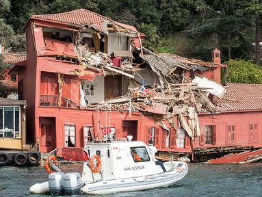 Sebuah perahu penjaga pantai menuju gedung bersejarah yang rusak di pantai Bosphorus, Istanbul, Turki (7/4). Gedung Hekimbasi Salih Efendi itu rusak berat usai ditabrak kapal tanker. (AFP Photo/Gurcan Ozturk)