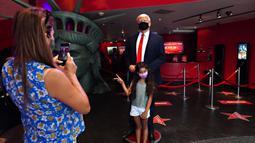 Seorang anak berfoto dengan sosok Donald Trump yang bermasker saat Madame Tussauds New York dibuka kembali di New York City, Kamis (27/8/2020). Patung lilin Donald Trump akan berada di pintu masuk untuk mengingatkan tentang protokol kesehatan, termasuk mengenakan masker. (Cindy Ord/Getty Images/AFP)