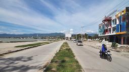 Kendaraan melintas di Pantai Talise (kiri) dan pusat bisnis Palu, Rabu (3/4). Bencana gempa dan tsunami yang melanda Palu pada 28 September 2018 lalu menewaskan 4.340 korban jiwa. (OLAGONDRONK/AFP)