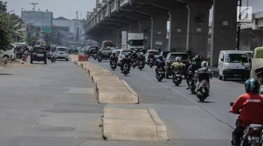 Kendaraan melintas dekat trotoar yang berada di tengah jalan di kawasan Kalimalang, Senin (16/9/2019). Selain dikeluhkan pengendara karena membahayakan, keberadaan trotoar tak lazim itu dinilai mempersempit jalan dan kerap menimbulkan macet saat jam sibuk. (Liputan6.com/Faizal Fanani)
