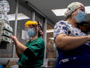 Perawat Chile, Damaris Silva memainkan biola untuk pasien yang terinfeksi COVID-19 di Unit Perawatan Intensif rumah sakit El Pino di Santiago pada 9 Juli 2020. Kegiatan tersebut dilakukan perempuan 26 tahun itu dua kali dalam seminggu setelah shift bekerjanya selesai. (Martin BERNETTI / AFP)