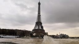 Menara Eiffel terlihat saat sungai Seine di Paris meluap, Prancis (6/1). Sungai Seine tidak mampu menampung debit air setelah hujan terjadi terus-menerus. (AFP Photo/Christophe Simon)