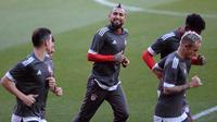 Gelandang Bayern Munchen, Arturo Vidal melakukan pemanasan dalam sesi latihan di Stadion Ramon Sanchez Pizjuan di Sevilla (2/4). Munchen akan bertanding melawan Sevilla pada leg pertama babak perempatfinal Liga Champions. (AFP Photo/Cristina Quicler)