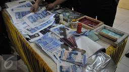 Polres Jakarta Barat merilis uang palsu, Jakarta, Jumat (25/9/2015). Tersangka dan barang bukti alat pencetak uang palsu berhasil diamankan petugas. (Liputan6.com/Gempur M Surya)