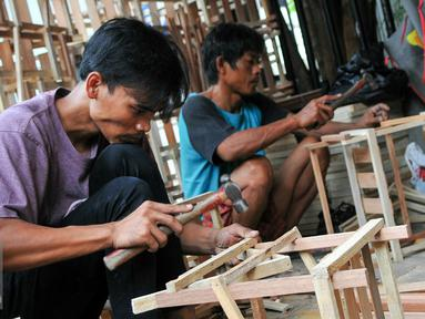 Pekerja menyelesaikan rangka kayu yang akan digunakan untuk parsel, Jakarta, Selasa (21/6). Menjelang Lebaran, pengrajin kerangka parsel mulai kebanjiran pesanan. (Liputan6.com/Yoppy Renato)