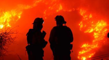 Dua petugas pemadam kebakaran mengecek api di atas Shepard Mesa Road di Carpinteria, California (10/12). Sejumlah warga di wilayah ini berhasil dievakuasi setelah api melalap permukiman mereka. (Mike Eliason/Santa Barbara County Fire Department via AP)