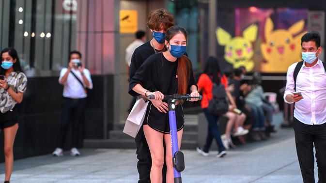 Sepasang muda-mudi mengenakan masker mengendarai skuter di sebuah jalan di Kuala Lumpur, Malaysia (24/11/2020). Malaysia pada Selasa (24/11) melaporkan 2.188 kasus baru COVID-19 dalam lonjakan harian tertinggi sejak wabah coronavirus merebak di negara itu. (Xinhua/Chong Voon Chung)
