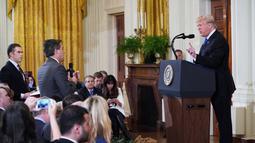 Presiden AS, Donald Trump terlibat adu mulut dengan jurnalis CNN, Jim Acosta (tengah) saat konferensi pers di Gedung Putih sesaat setelah pemilu sela digelar, Rabu (7/11). Ketegangan bermula dari pertanyaan sang wartawan soal imigran. (MANDEL NGAN/AFP)