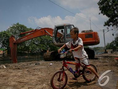 Seorang bocah bersepeda asyik memperhatikan pengerukan Kali Sidang, Jakarta, Jumat (19/9/2014) (Liputan6.com/Faizal Fanani)