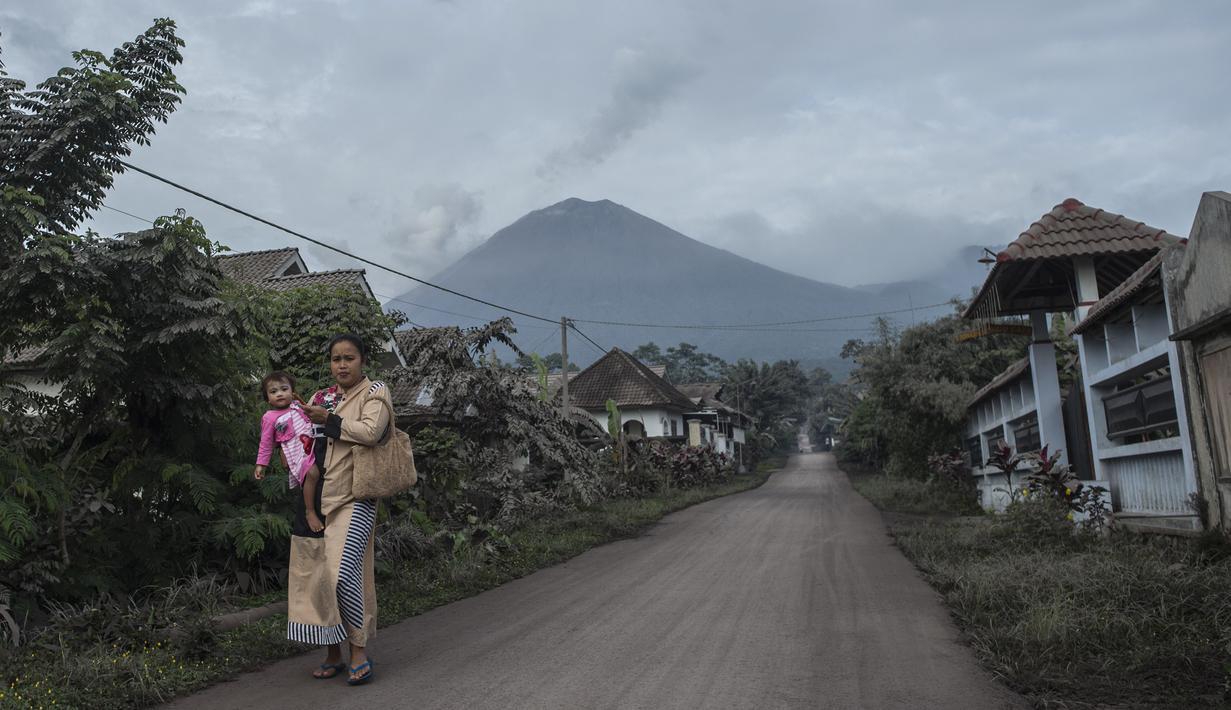 Gunung Semeru menjulang di atas desa Lumajang, Jawa Timur, setelah meletus sehari sebelumnya, Minggu (17/1/2021). Gunung Semeru kembali erupsi dan mengeluarkan awan panas guguran sejauh 4,5 kilometer pada Sabtu (16/1). (Juni Kriswanto / AFP)