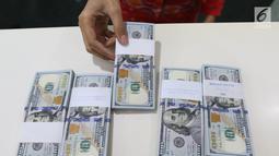 Teller menunjukkan mata uang dolar di Bank Mandiri, Jakarta, Kamis (10/1). Nilai tukar rupiah terhadap dolar Amerika Serikat (AS) terus menguat di perdagangan pasar spot hari ini. Rupiah berada di zona hijau. (Liputan6.com/Angga Yuniar)