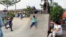 Seorang anak bermain meluncur di area Skate Park RPTRA Kalijodo, Jakarta, Sabtu (15/6/2019). Menjelang sore hari, anak-anak berdatangan menghabiskan waktu dengan bermain di area RPTRA Kalijodo. (Liputan6.com/Helmi Fithriansyah)
