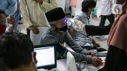 Petugas kesehatan memeriksa suhu tubuh seorang pemuka agama sebelum menjalani Vaksinasi COVID-19 di Mesjid Istiqlal, Jakarta, Selasa (23/2/2021). Pemuka agama yang mengikuti vaksinasi ini mencapai ribuan orang. (Liputan6.com/Faizal Fanani)