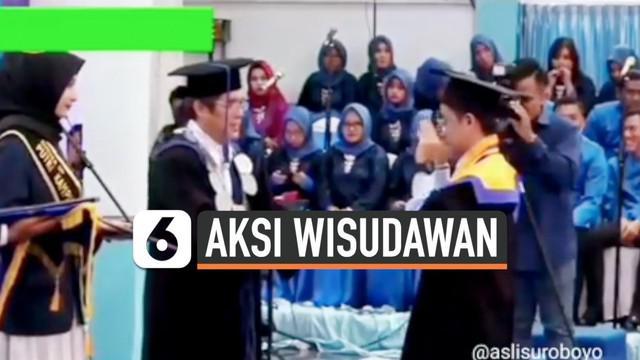 """Seorang wisudawan asal Surabaya lakukan aksi gerakan tangan meniru gaya dari lagu """"Entah Apa Yang Merasukimu"""" saat pembagian ijazah oleh Rektor. Aksinya tersebut menarik perhatian warganet dan bikin ngakak."""