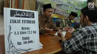 Petugas bersama seorang pria berdoa usai membayarkan zakat fitrah di Masjid Istiqlal, Jakarta, Jumat (23/6). Waktu pembayaran dibuka hingga malam takbiran dengan pembayaran zakat senilai Rp50ribu dan beras 3,5 liter. (Liputan6.com/Helmi Afandi)