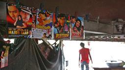 Seorang pria berjalan ke luar bioskop darurat di bawah jembatan di India (25/5). Untuk menghibur warga kurang mampu yang menyukai musik dan film Bollywood, tempat ini menayangkan sebanyak 4 film dalam sehari. (REUTERS/Cathal McNaughton)