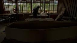 Sphiwe Maseko mengerjakan pembuatan peti mati di bengkelnya, Evaton, selatan Johannesburg, Afrika Selatan, Senin (15/2/2021). Maseko mengatakan, bahan dan biaya pembuatan peti mati telah naik karena pemasok yang lebih sedikit dampak pandemi COVID-19. (AP Photo/Themba Hadebe)