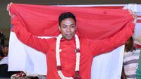 Pelari muda Indonesia, Lalu Muhammad Zohri membentangkan bendera Merah Putih saat penyambutan di Terminal 3 Bandara Soetta, Tangerang, Selasa (17/7). Lalu M Zohri meraih emas 100m putra di Kejuaraan Dunia Atletik U-20. (Liputan6.com/Helmi Fithriansyah)