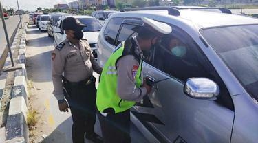 Personel Polresta Pekanbaru memeriksa kendaraan di pos penyekatan larangan mudik.