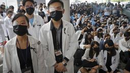 Perawat dan staf medis mengenakan penutup mata dan masker saat unjuk rasa di sebuah rumah sakit di Hong Kong (13/8/2019). Mereka memprotes kebrutalan polisi yang menurut mereka terjadi selama demonstrasi anti-pemerintah berlangsung pada akhir pekan. (AP Photo/Kin Cheung)