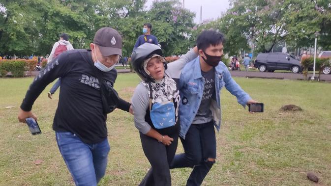 Dua orang mahasiswa di Palembang membantu salah satu pedagang menyelamatkn diri dari amukan pendemo (Liputan6.com / Nefri Inge)