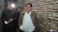Gambar tak bertanggal yang dirilis pada 19 November 2019, pemimpin Korea Utara Kim Jong-un (kanan) mengunjungi pabrik pengolahan ikan di lokasi yang dirahasiakan di Korea Utara. Kim Jong-un berbicara dengan para pekerja dan sesekali tertawa saat berkeliling pabrik.  STRINGER/KCNA VIA KNS/AFP)