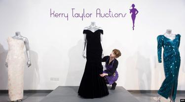 Seorang staf di balai lelang Kerry Taylor Auction di London, 15 Maret 2013, berpose dengan gaun malam Victor Edelstein (tengah) yang digunakan Putri Diana dalam acara jamuan makan malam kenegaraan di Gedung Putih pada 1985.