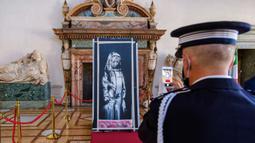 Seorang perwira Gendarmerie Prancis memfoto Lukisan seniman Inggris Banksy yang menggambarkan sosok perempuan muda dengan ekspresi sedih di Kedutaan Besar Prancis di Roma (14/7/2020). Karya seni itu dicuri pada 2018.  (AP/Photo/Domenico Stinellis)