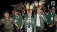 Ketua Umum PKB, Muhaimin Iskandar alias Cak Imin mengenakan topi khas Papua saat mendatangi Gedung KPU RI, Jakarta, Minggu (18/2). Cak Imin mendatangi KPU untuk pengundian nomor urut partai politik peserta pemilu 2019. (Liputan6.com/Faizal Fanani)