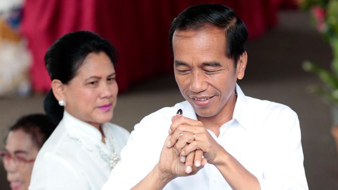 Calon Presiden Nomor Urut 01 Joko Widodo atau Jokowi menunjukkan jari yang telah dicelup tinta usai melakukan pencoblosan dalam Pemilu 2019 di TPS 008 Gambir, Jakarta Pusat, Rabu (17/4). Jokowi dan Iriana terdaftar di nomor urut 154 dan 155 daftar DPT. (AP/Dita Alangkara)