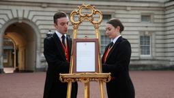 Pelayan kerajaan Stephen Kelly dan Sarah Thompson membawa papan pengumuman kelahiran anak pertama Pangeran Harry dan Meghan Markle di London, Inggris, Senin (6/5/2019). Dalam tradisi kerajaan, setiap kelahiran bayi akan diumumkan di depan Istana Buckhingham. (Yui Mok/Pool Photo via AP)