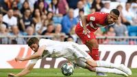 Gelandang Real Madrid, Federico Valverde, dijatuhkan gelandang Granada, Yangel Herrera, pada laga La Liga Spanyol di Stadion Santiago Bernabeu, Madrid, Sabtu (5/10). Madrid menang 4-2 atas Granada. (AFP/Pierre-Philippe Marcou)