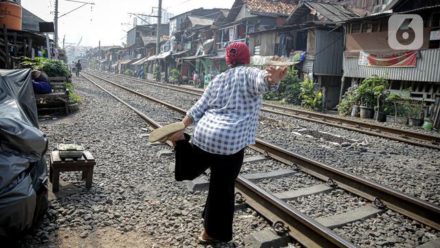 Warga berolah raga ringan sambil berjemur di bantaran rel di kawasan pemukiman padat Pejompongan, Jakarta, Selasa (6/7/2021). Berjemur diri di bawah matahari di antara pukul 08.00-11.00 WIB merupakan salah satu upaya menjaga kesehatan selama wabah virus COVID-19. (Liputan6.com/Faizal Fanani)