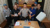 Kapolresta Solo AKBP Andy Rifai menunjukka barang bukti bahan pembuat miras oplosan yang tewaskan lima orang di Solo.(Liputan6.com/Fajar Abrori)
