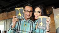 """Pasangan Andhika Pratama dan Ussy Sulistyawati memperlihatkan buku biografi mereka berjudul """"Bukan Cinta Cinderella"""" saat acara perilisan di Lippo Mall Kemang, Jakarta, Jumat (22/5). (Liputan6.com/Panji Diksana)"""